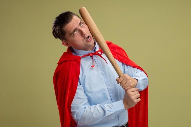 明るい背景の上に立っている野球のバットで自分自身をパンチする赤いマントのスーパーヒーローの実業家