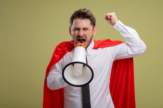 Супергерой бизнесмен в красной накидке кричит в мегафон с агрессивным выражением лица, поднимая кулак, стоя над зеленой стеной