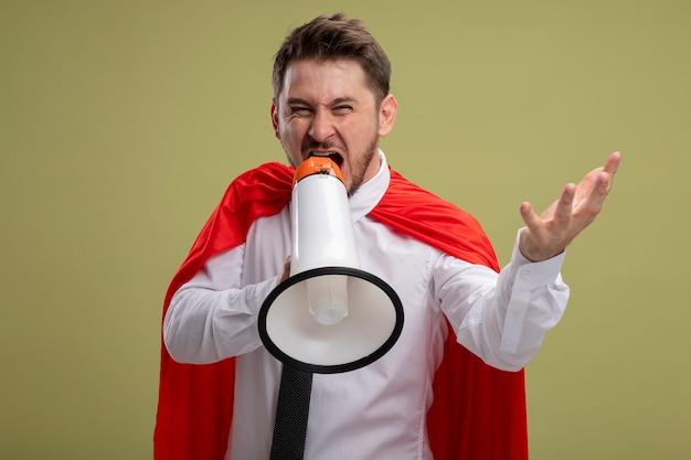 緑の背景の上に立っている腕で攻撃的な表現でメガホンに叫んでいる赤いマントのスーパーヒーローの実業家