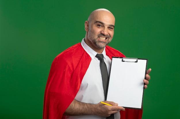 緑の壁の上に立っている顔に笑顔で正面を見て空白のページでクリップボードを示す赤いマントのスーパーヒーローの実業家