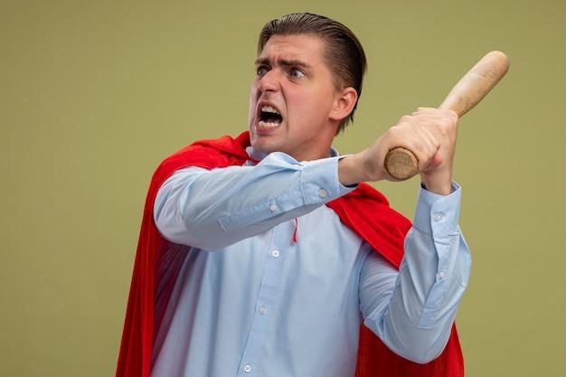明るい背景の上に立っている攻撃的な表情で野球のバットを振る赤いマントのスーパーヒーローの実業家