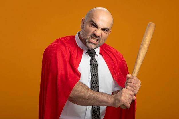 怒っている攻撃的な表情で野球のバットを振る赤いマントのスーパーヒーローの実業家