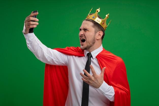 Супер герой бизнесмен в красном плаще в короне делает селфи с помощью смартфона, сходит с ума, злой, стоя на зеленом фоне