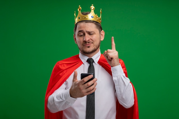 녹색 배경 위에 새로운 아이디어가 서있는 데 미소 검지 손가락을 보여주는 스마트 폰을 사용하여 왕관을 쓰고 빨간 케이프에서 슈퍼 영웅 사업가