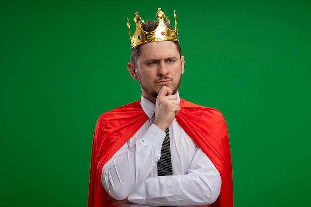 緑の壁の上に立って自信を持って真剣な表情を考えてあごに手で王冠を身に着けている赤いマントのスーパーヒーローの実業家