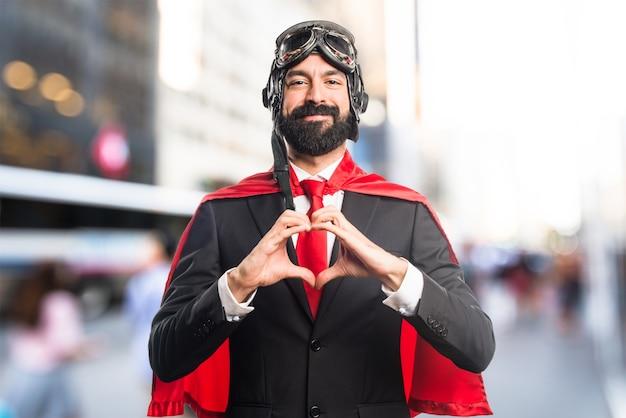 Uomo d'affari super eroe fare un cuore con le mani