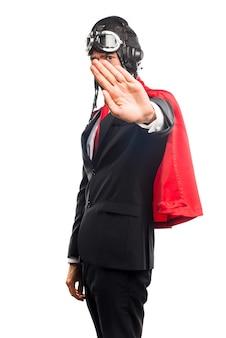 Супер герой бизнесмен делает знак остановки