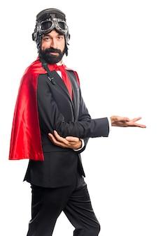 Super hero businessman presenting something