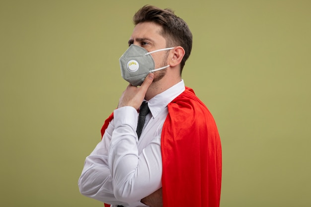 Super hero businessman in protective facial mask and red cape looking aside with hand on chin thinking with serious look standing over green background