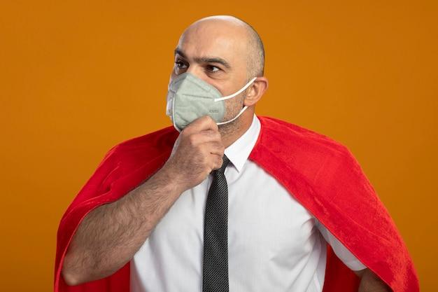Uomo d'affari super eroe in maschera facciale protettiva e mantello rosso che guarda da parte con espressione pensierosa sul viso con la mano sul mento pensando in piedi sopra la parete arancione