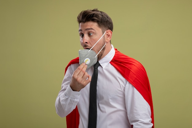 Super hero businessman in protective facial mask and red cape looking confused taking mask off standing over green background