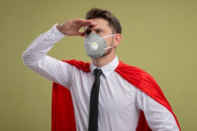 Uomo d'affari super eroe in maschera facciale protettiva e mantello rosso che guarda lontano con la mano sopra la testa in piedi sul muro verde
