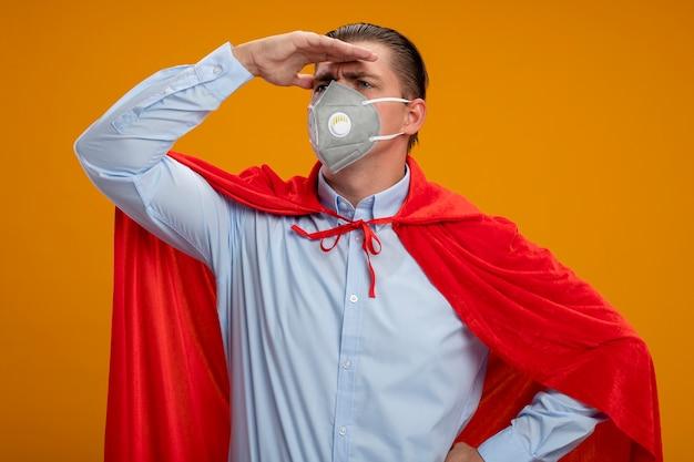 Uomo d'affari super eroe in maschera facciale protettiva e mantello rosso che guarda lontano con la mano sopra la testa in piedi sopra la parete arancione