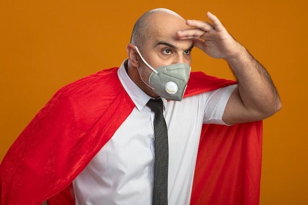 Uomo d'affari super eroe in maschera facciale protettiva e mantello rosso che guarda lontano con la mano sopra la testa in piedi sul muro arancione