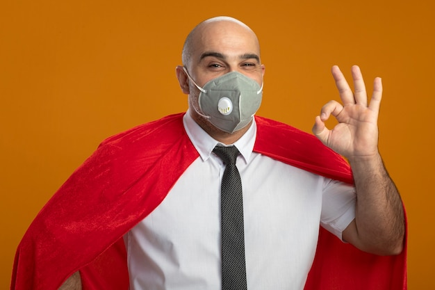 Super hero businessman in protective facial mask and red cape looking at front smiling showing ok sign standing over orange wall