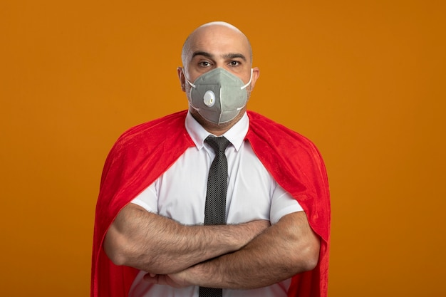 Super hero businessman in protective facial mask and red cape looking at front with crossed hands on chest with serious frowning face standing over orange wall