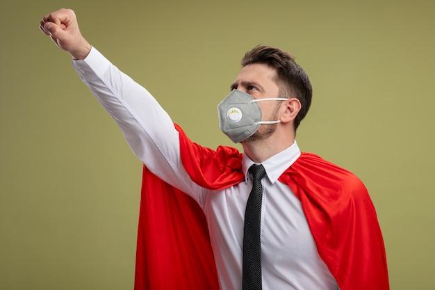 Uomo d'affari super eroe in maschera facciale protettiva e mantello rosso che fa il gesto vincente cercando fiducioso pronto ad aiutare in piedi sopra la parete verde