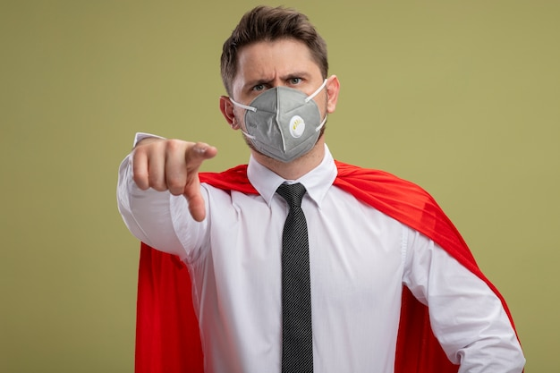 Super hero businessman in protective facial mask and red cape pointing with index finger at you looking confident being displeased standing over green background