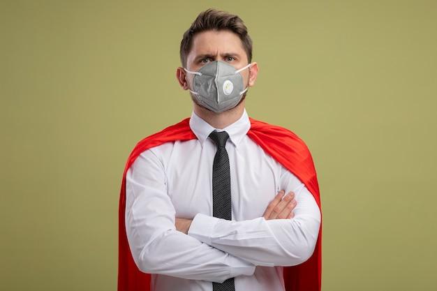 Uomo d'affari super eroe in maschera facciale protettiva e mantello rosso con le mani incrociate sul petto con grave faccia accigliata in piedi sopra la parete verde