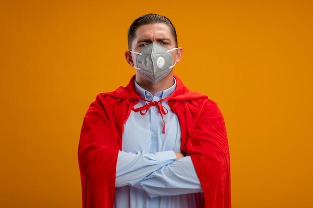 Uomo d'affari super eroe in maschera facciale protettiva e mantello rosso con le mani incrociate sul petto con grave faccia accigliata in piedi sopra la parete arancione