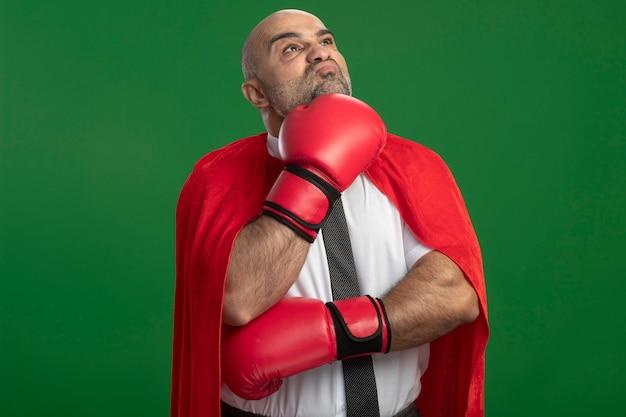 Uomo d'affari super eroe in mantello rosso e guantoni da boxe guardando da parte con espressione pensierosa sul viso con la mano sul mento in piedi sopra la parete verde