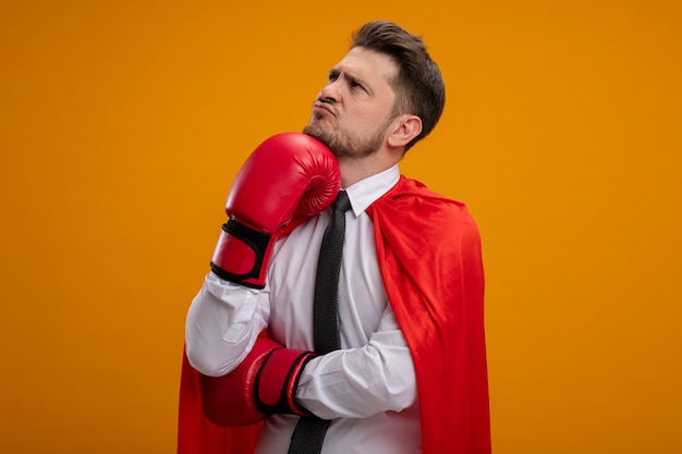 Super hero businessman in red cape and in boxing gloves looking aside with pensive expression on face with hand on his chin standing over orange wall
