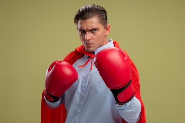 Uomo d'affari super eroe in mantello rosso e guantoni da boxe che guarda l'obbiettivo con la faccia seria pronta a combattere in piedi su sfondo chiaro