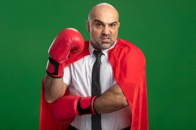 Uomo d'affari super eroe in mantello rosso e guantoni da boxe guardando davanti confuso e scontento con la mano alzata in piedi sopra la parete chiara