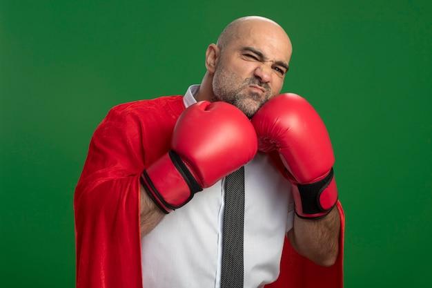 Uomo d'affari super eroe in mantello rosso e guantoni da boxe guardando davanti con espressione confusa in piedi sopra la parete verde