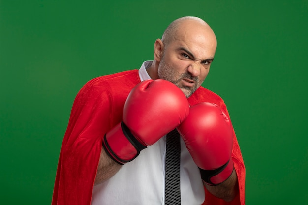 Uomo d'affari super eroe in mantello rosso e guantoni da boxe guardando davanti con faccia seria pronta a combattere in piedi sopra la parete verde