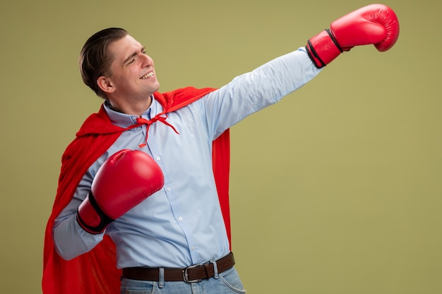 Super hero businessman in red cape and in boxing gloves making winning gesture with hand smiling confident ready to fight standing over light background