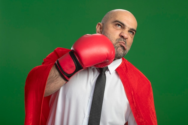 Super hero businessman in red cape and in boxing gloves punching himself