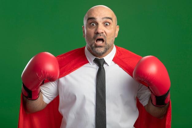 Uomo d'affari super eroe in mantello rosso e guantoni da boxe alzando le mani guardando davanti spaventato gridando in piedi sopra la parete chiara