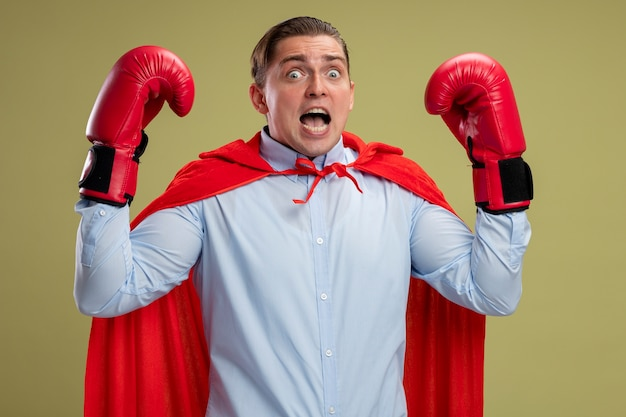 Super hero businessman in red cape and in boxing gloves raising hands  scared shouting standing over light wall