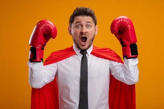 Uomo d'affari super eroe in mantello rosso e guantoni da boxe alzando le mani spaventato gridando in piedi sopra la parete arancione