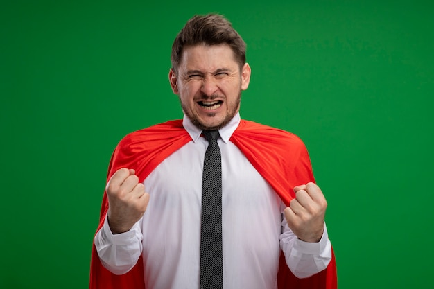Super hero businessman in red cape clenching fists emotional and excited standing over green background