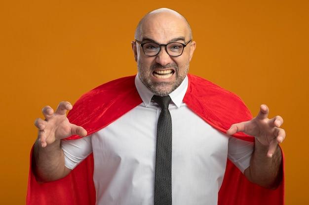 Uomo d'affari super eroe in mantello rosso e occhiali arrabbiati e frustrati guardando davanti che urla con le braccia alzate in piedi sopra la parete arancione