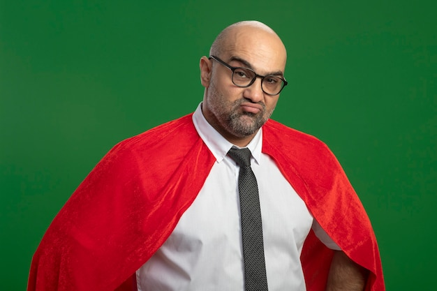 Super hero businessman in red cape and glasses being displeased