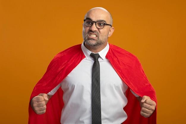 Uomo d'affari super eroe in mantello rosso e occhiali che stringono i pugni arrabbiati e frustrati