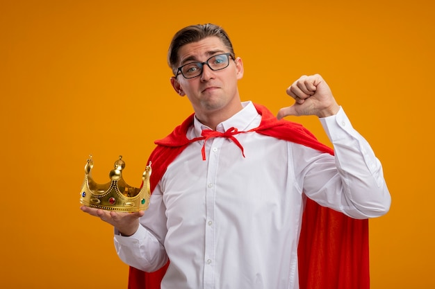 Super hero businessman in red cape and glasses holding crown pointing at himself smiling confident standing over orange wall