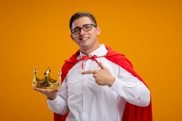 Super hero businessman in red cape and glasses holding crown pointing with index finger at it smiling confident standing over orange background