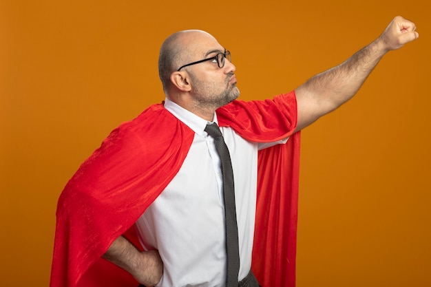 Super hero businessman in red cape and glasses looking aside keeping arm in flying gesture ready to help