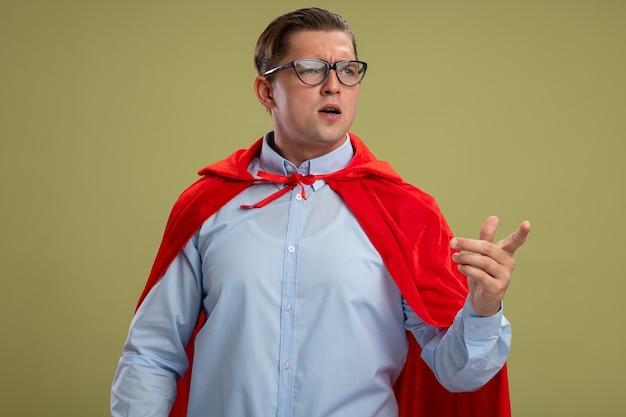 Super eroe uomo d'affari in mantello rosso e occhiali guardando da parte in piedi perplesso su sfondo chiaro