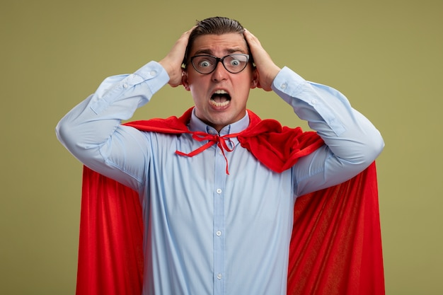 Super hero businessman in red cape and glasses looking at camera being crazy amazed and surprised touching his head standing over light background