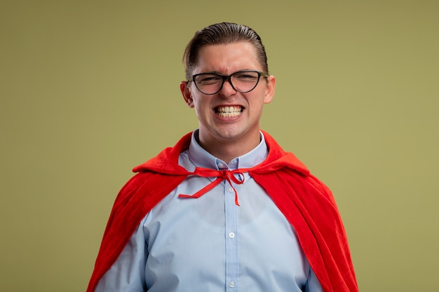 Super hero businessman in red cape and glasses looking at camera smiling broadly showing his teeth standing over light background