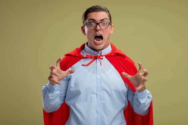 Uomo d'affari super eroe in mantello rosso e occhiali che grida con le mani alzate pazzo pazzo andando selvaggio in piedi su sfondo chiaro