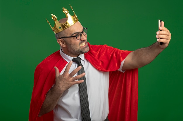 Super hero businessman in red cape and glasses wearing crown doing selfie using smartphone going wild crazy angry standing over green wall