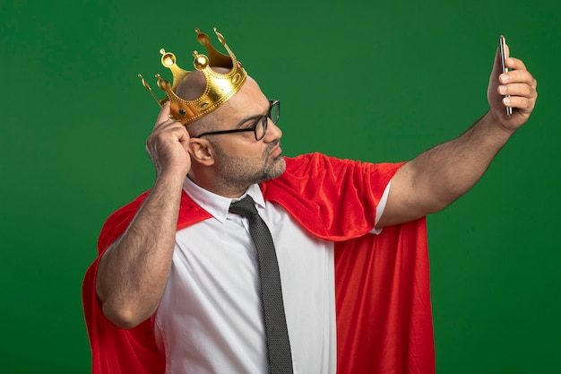 Super hero businessman in red cape and glasses wearing crown doing selfie using smartphone