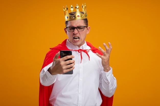 Uomo d'affari super eroe in mantello rosso e occhiali che indossa la corona che tiene smartphone guardandolo con il braccio alzato in piedi arrabbiato e frustrato su sfondo arancione