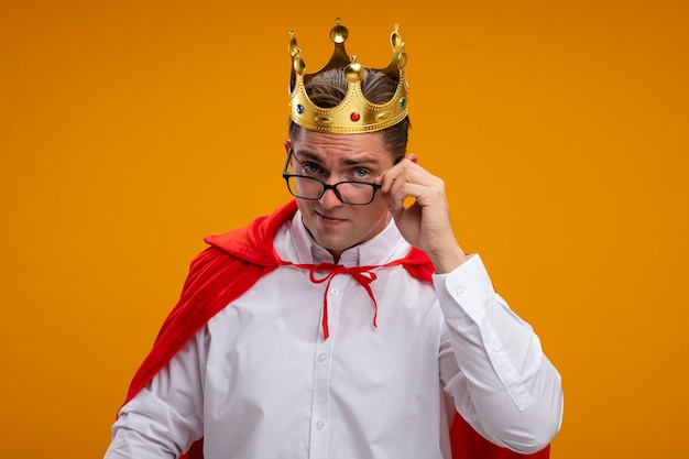 Super hero businessman in red cape and glasses wearing crown lookign at camera being intrigued standing over orange background